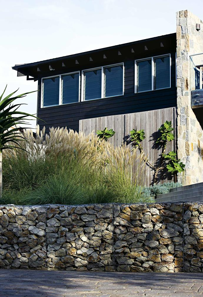 "**TURN TO STONE** The horizontal lines of the gabion wall repeat those of the [timber-clad house](https://www.homestolove.com.au/exterior-cladding-options-20504|target=""_blank""). Not only creating an edging wall to the parking area, the quartz-filled gabion baskets also retain the slope behind, which is planted with a variety of grasses and groundcovers. The screen of 50mm x 50mm merbau pickets encloses the [outdoor shower zone](https://www.homestolove.com.au/outdoor-shower-ideas-19532
