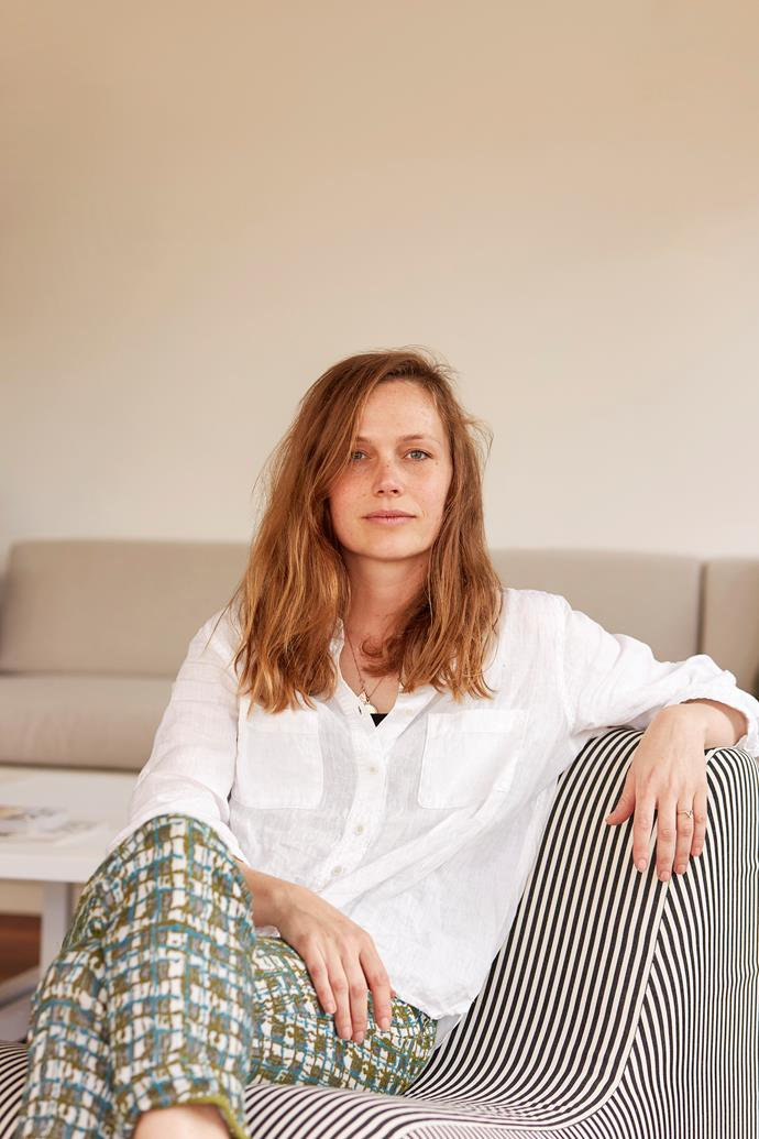 """""""I'm still learning to take risks with colour,"""" says Olivia, pictured reclining in the lounging area on a chair she bought on Gumtree and reupholstered in Zepel Fabrics' Geologic Eclipse."""