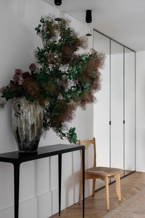 """In the entrance, mirrored cupboards create dimension, while """"a Jean-Michel Frank-inspired console and a 1940s French chair provide delicate yet strong silhouettes"""" against the pale walls and floor. Console by MacGyver Models. Chair, 1stdibs. Turkish runner, MCM House. Jann Kesby vase, Bess Paddington."""
