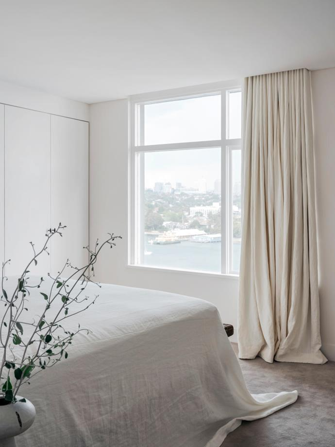 Linen furnishings and soft grey Fabrica Dolce carpet from Whitecliffe Imports set a meditative tone in this harbour-facing bedroom. The bedhead and blockout curtains are crafted from Altamira stonewash linen. Bedding, Velvet Valley. Bench, Orient House.