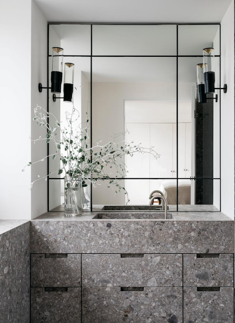 The bedroom ensuite boasts custom stonework by Granite & Marble Works and a mirror by Kenneth Kamp. The honed Ceppo limestone vanity with an integrated sink is the centrepiece.