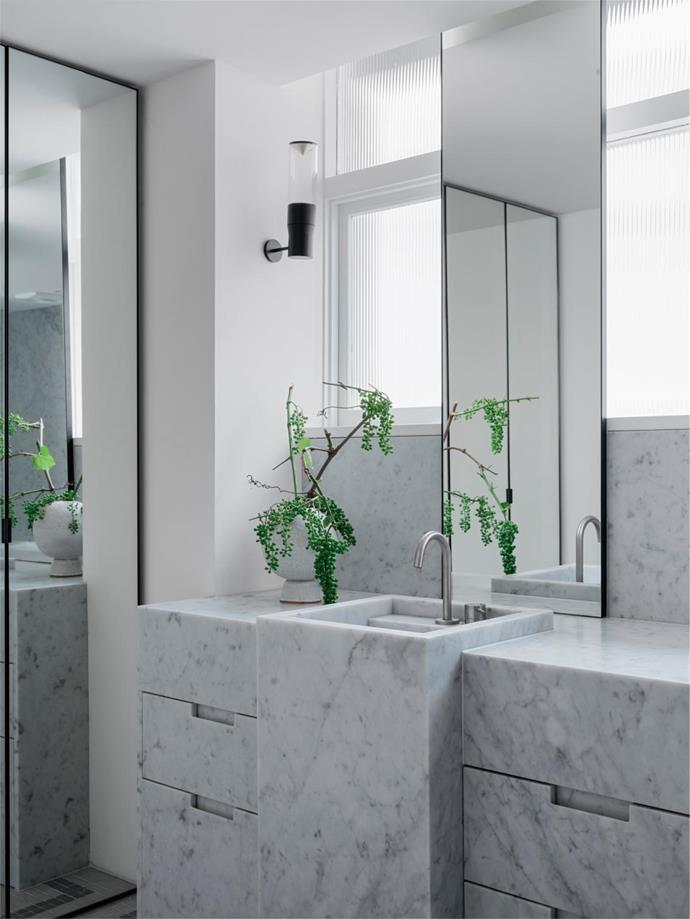 The ceiling and windowsill heights in the main bathroom didn't match up with other rooms, so Tania and Gillian were tasked with installing a new ceiling and turning the raised windowsill into a feature with a stunning marble splashback. On the Carrara benchtop is a vessel by Emma Young filled with greenery from Bess Paddington.