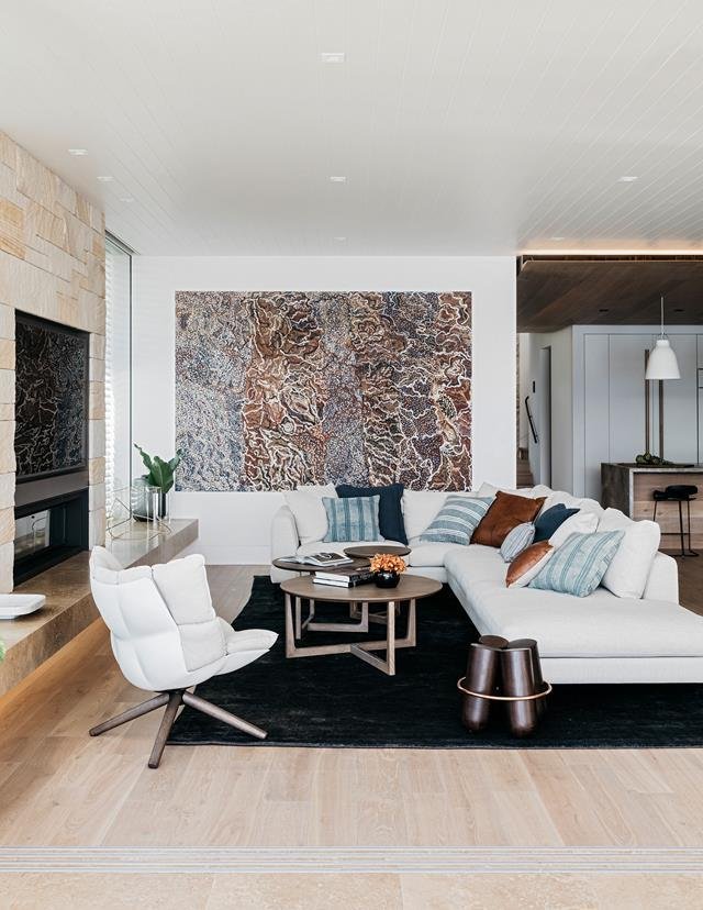 "ID\Studios AI gave this [Palm Beach abode](https://www.homestolove.com.au/redesign-of-an-old-beach-house-6011|target=""_blank"") a contemporary coastal redesign. A large-scale work by Indigenous artist Mavis Ngallametta sets the tone in this warm-toned living room. Though it is a coastal home, a fireplace and soft furnishings ensure this space is the ideal spot to relax in the winter months."