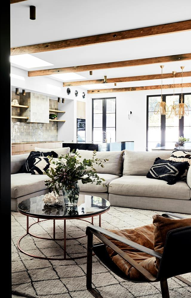 "Recycled tallowood beams were added into this [family room](https://www.homestolove.com.au/a-modern-rustic-family-home-with-artisanal-appeal-6366|target=""_blank"") which has a modern, rustic aesthetic. Leanne Smeallie's use of layering and incorporation of textures has given this space decidedly winter vibe."