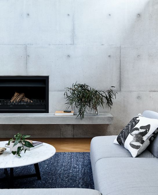 "A native plant palette softens the weighty concrete forms and raw timbers grounding this [family home](https://www.homestolove.com.au/mornington-peninsula-home-by-planned-living-architects-5597|target=""_blank"") in a coastal zone. Blackbutt timber flooring offsets the cool tones of the space, and a sleek fireplace offers plenty of warmth."