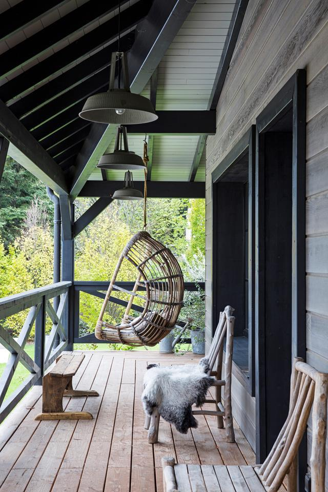 """An egg swing makes for a relaxing outdoor reading spot on the verandah of an [interior designer's Scandi home](https://www.homestolove.com.au/a-scandi-home-with-eclectic-style-7013