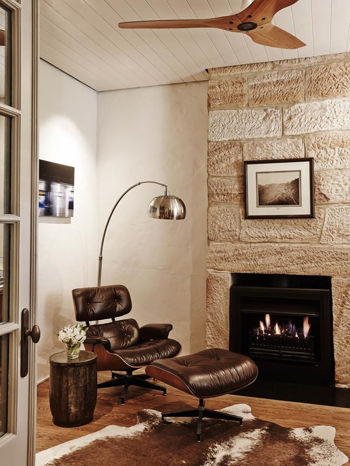 """An original Eames chair and stool are ideally situated next to an open fire in [this historic cottage](https://www.homestolove.com.au/heritage-cottage-with-a-modern-extension-3879