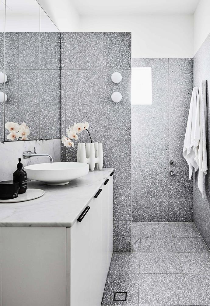 "In [interior designer Kristy McGregor's home](https://www.homestolove.com.au/kristy-mcgregor-house-21306|target=""_blank""), grey terrazzo tiles create a stunning visual feature in the bathroom. The subtle marble vanity and white cabinetry add an understated contrast to the rest of the space."
