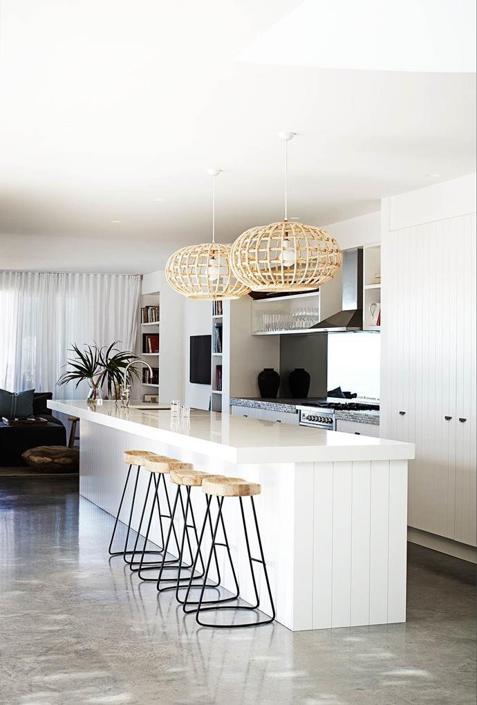 "Cane pendants combined with timber panelled kitchen cabinetry  by Haughey Group, add to the beachy feel of this [weatherboard home on Sydney's northern beaches](https://www.homestolove.com.au/weatherboard-home-with-wow-factor-3458|target=""_blank"")."