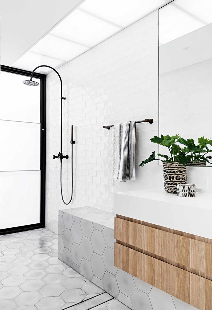 "In the muted bathroom of the [bathroom in this wabi-sabi inspired Perth home](https://www.homestolove.com.au/wabi-sabi-meets-warehouse-style-living-in-this-perth-home-18946|target=""_blank""), white subway tiles are paired with pale grey hexagon tiles and a timber vanity for added depth."