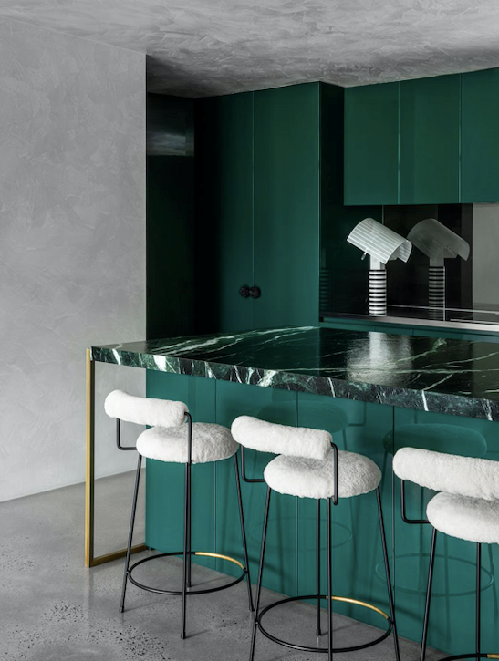 Echoing the greens of the exterior landscape, the kitchen glows in a rich, dark combination of Corsi & Nicolai Verde Rameggiato marble on the island bench and glossy joinery finished in Resene 'Celtic'. 'Iva' stools in powdercoated steel and brass upholstered in sheepskin from Grazia & Co. Artemide 'Shogun Tavolo' table lamp by Mario Botta.
