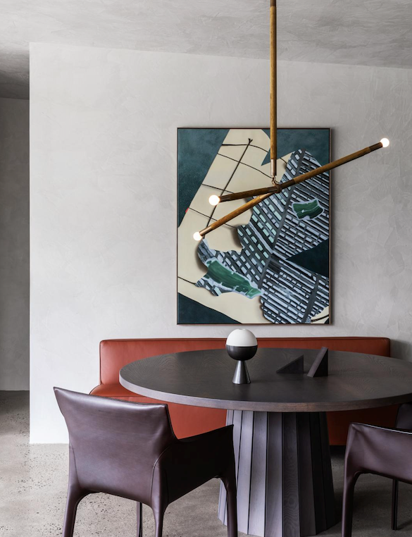 In the meals area, an Apparatus 'Arrow' bronze pendant light from Criteria is centred over a Moooi 'Container' table from Space with 'Saddle' armchairs by Walter Knoll from Living Edge. Gubi bench seat from Criteria below Tilting at Space (2019) by Alice Wormald from Daine Singer.