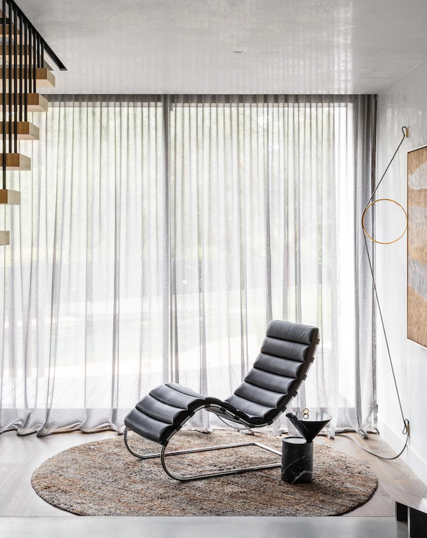 On a circular rug from Armadillo & Co in the entry, the Knoll 'Mr Chaise' lounge in bellagio leather from De De Ce offers a quiet spot in which to read or relax under the Flos 'Wirering Grey' wall light from Euroluce. De La Espada 'Laurel' side table from Criteria. Artwork by Eunice Napanangka Jack.