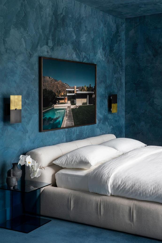 Polished-plaster walls and ceiling have been finished using Resene 'Cello', a deep blue-grey. B&B Italia 'Tufty' bed from Space. Apparatus 'Pivot' sconces from Criteria on the wall flank the photographic artwork by Tom Blachford from 'Midnight Modern Series II'. SuperTuft Escape Velour 'Aisha' carpet. e15 'Vier' side table in dark-blue glass from Living Edge.