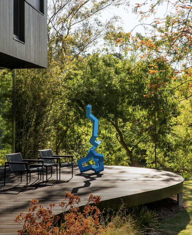 View from the master bedroom out to the lush surrounds and the deck with a sculpture by Caleb Shea from Lon Gallery and Knoll 'Schultz' lounge chairs from De De Ce.