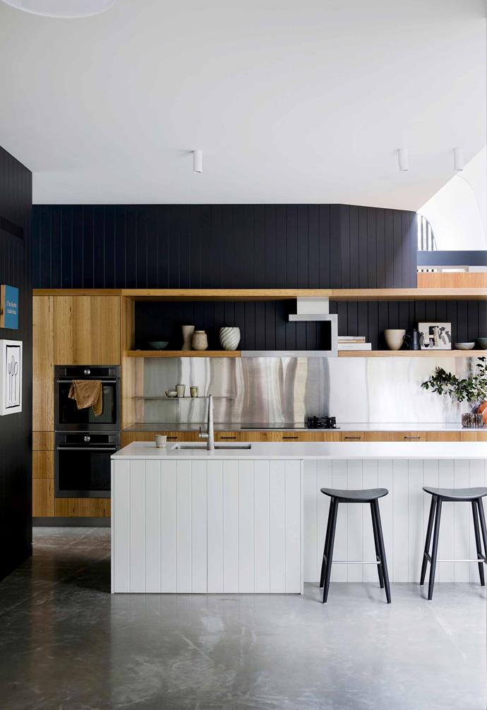 In this nature-inspired home in Riverview a rich material palette comes together to incredible effect. In the kitchen concrete floors are paired with dark panelled walls, timber cabinetry, and a hero kitchen island topped with a marble benchtop. The rear bench features a stainless steel splashback and bench top for a modern touch.