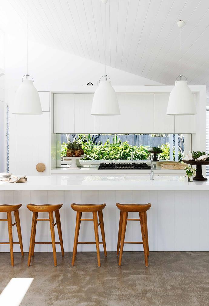In this renovated fibro cottage in Avalon, crisp white cabinetry is paired with concrete flooring and a trio of sculptural pendant lights above the kitchen island. For the benches, this family opted for Corian benchtops in Glacier White. As a solid surface material, it can be a sturdier choice than laminate.