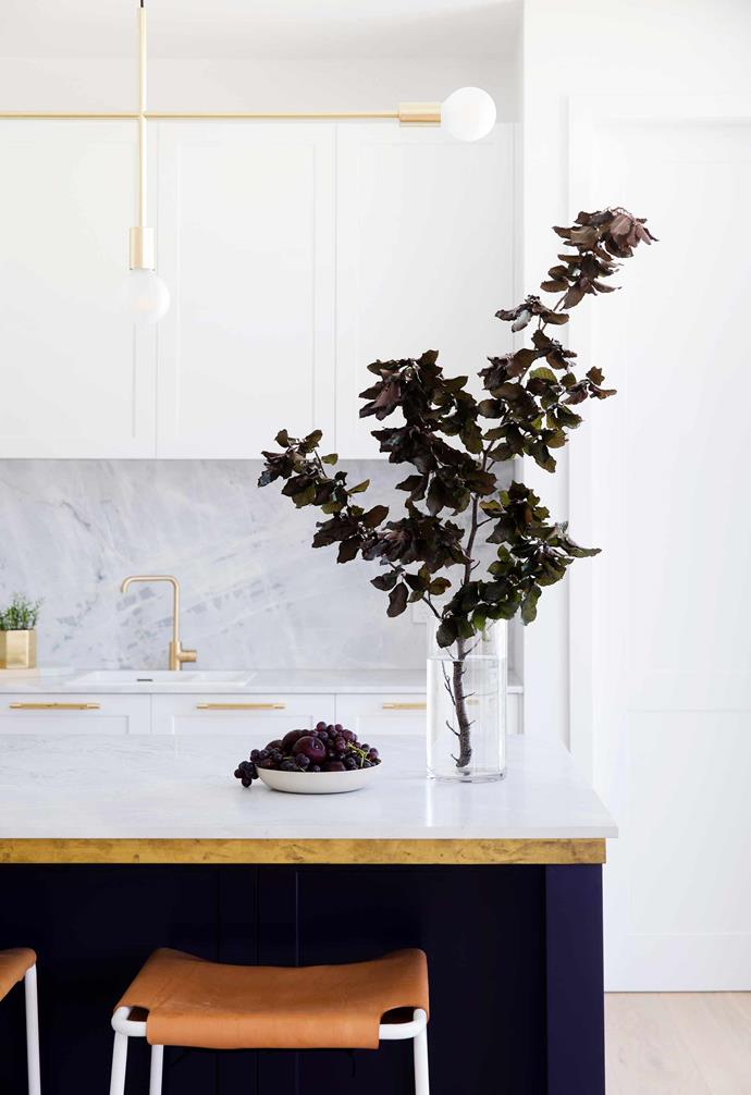 "Luxurious Elba marble was chosen for the splashback and bench top in the kitchen of this [all-white Hamptons-style home in Sydney](https://www.homestolove.com.au/all-white-hamptons-style-home-21036|target=""_blank""). Dark cabinetry and brushed gold fixtures add a glamourous contrast."