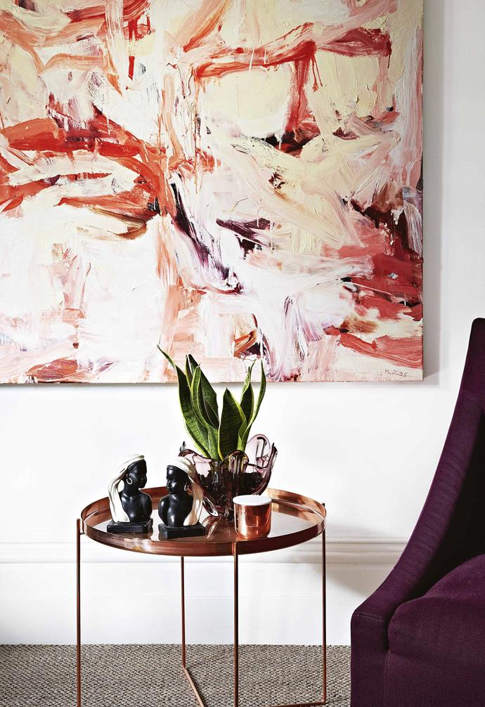 """**Star performer** Angela and John's enviable art collection informs the use of colour throughout the home. """"I like to draw on the colours in a painting and reflect them in fabrics, glassware and foliage in the room,"""" explains Angela. Sculptures on the table are by Emma Fenton."""