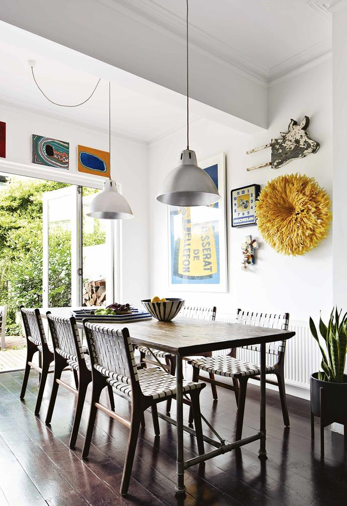 **Dining area** Two pendant lights, which John found at a warehouse sale and were from a Penguin Books printing factory, sit above a table and chairs from [Fenton & Fenton](https://www.fentonandfenton.com.au/). Artwork: Yikartu Bumba, Yikartu Bumba, Vintage Posters Only, Jai Vasicek.