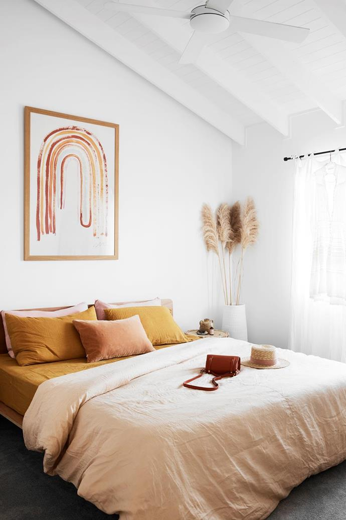 """The statement rainbow print by Tess Guinery above our bed makes me feel so happy every time I enter,' said Ellie Bullen of Elsa's Wholesome Life, who's the owner of this sunny bedroom in [her Gold Coast home](https://www.homestolove.com.au/ellie-bullen-gold-coast-home-20988