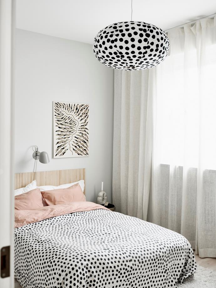"""We searched for a headboard for so long,"" Emilia says, ""but everything was so boring! So I made my own using MDF and half wooden dowel rods."" Polkadot bedlinen from Midnatt brings the design scheme together. An artwork by Linnea Andersson Ast hangs beside the Örsjö Belysning lamp."
