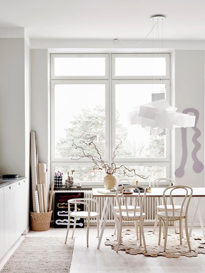 The high ceilings and expansive windows allow for light to illuminate the Scandi kitchen. The Hay dining table and second-hand Ikea chairs are the perfect minimalist base for Emilia's artistic touches like the statement Foscarini pendant, hairpin artwork and Anna-Lisa Thomson vase.