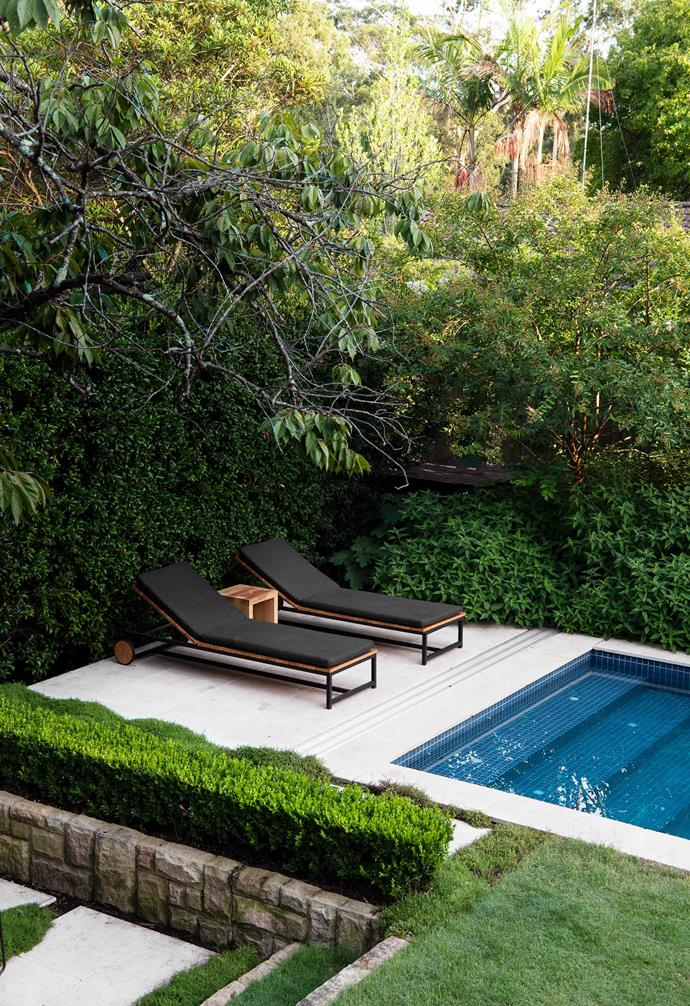 A tiled terrace at the end of the pool is one of the few pieces of hardscaping. The family likes to place their towels on the robust couch grass next to the pool.