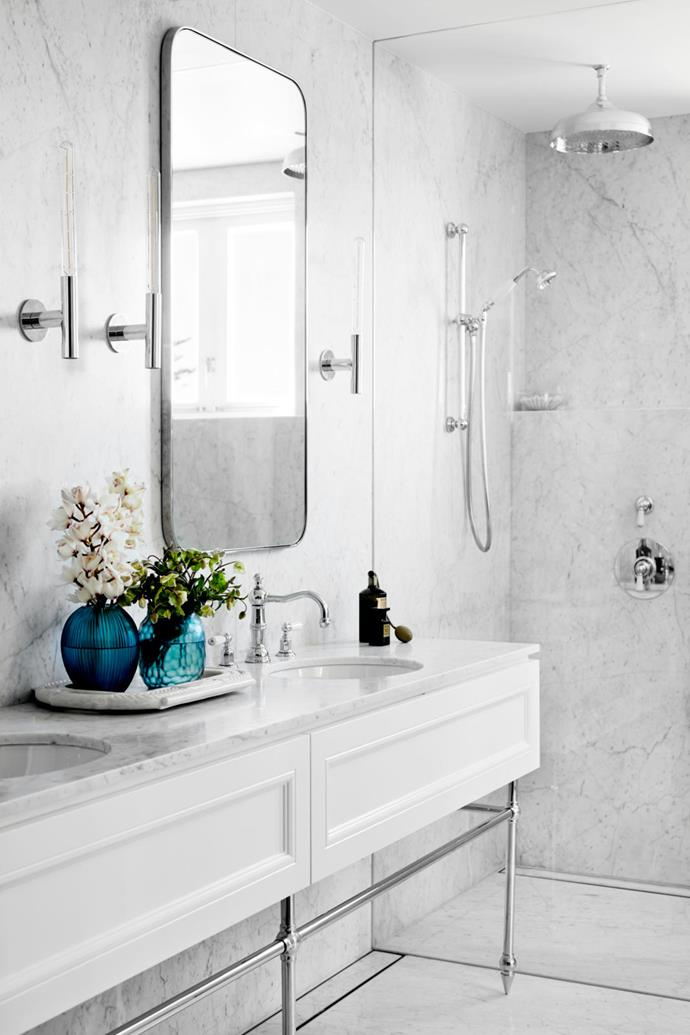 Slabs of Carrara marble envelop the renovated master ensuite. Chrome fixtures such as the Perrin & Rowe tapware and basin stand and the Giffin Design 'Candle' sconces keep the look polished. The joinery and mirrors were designed by Weir Phillips and made by Madison Turner.