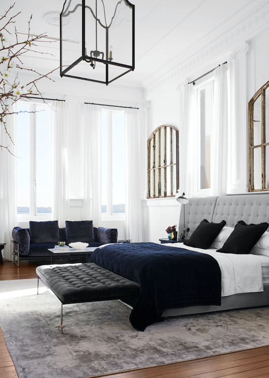 """At around 60 square metres, the master bedroom """"feels like we're in our own little piece of paradise,"""" says Dominique. Extra windows were installed to maximise the view; the added light now bounces off mirrors made using antique French windows by LuMu Interiors. The Flexform 'Caress' bed, the 'Zeno Light' sofa and the 'Magi' chaise are all from Fanuli. Sprawled across the super king bed is an Amara cotton velvet coverlet from Leilah; layered over the existing tallowwood floorboards is a Casablanca rug from Tribe Home."""