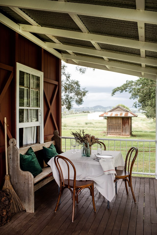 "An antique church pew forms part of a cosy outdoor dining setting on the verandah of a red [farmhouse in Queensland](https://www.homestolove.com.au/timber-farmhouse-sunshine-coast-21427|target=""_blank"")."