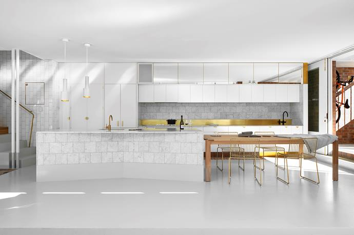 The white upper kitchen cabinets are framed by extra mirror-fronted storage, which adds 3D depth to a 2D wall. Artek 'A110 Hand Grenade' pendants illuminate one end of the kitchen island, leaving head room with their staggered heights.