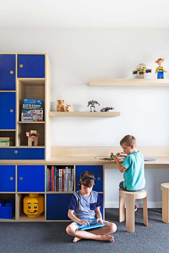 """Interior designer Adele Bates designed custom Laminex storage for her nephews' toys and books in their bedroom with Seasoned Oak, Royal and Olympia Blue shades, in their [Melbourne split-level home](https://www.homestolove.com.au/a-split-level-house-design-for-an-awkward-sloping-block-5141