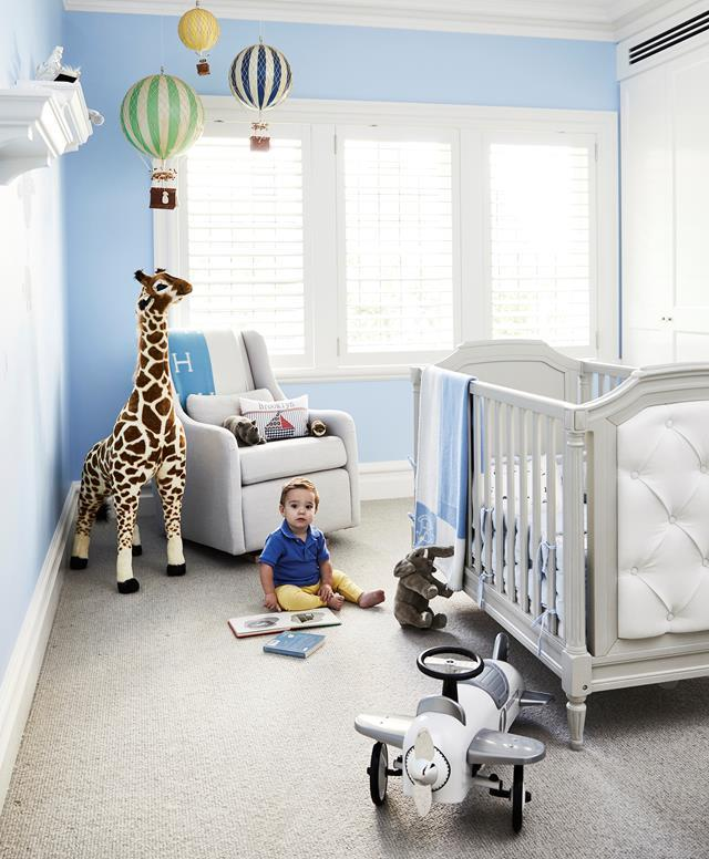 """Hot-air balloon decorations and a sizable giraffe are the charming additions to this baby boy's blue room in a [Hamptons style Art-Deco apartment](https://www.homestolove.com.au/art-deco-apartment-gets-a-hamptons-style-makeover-1-20999