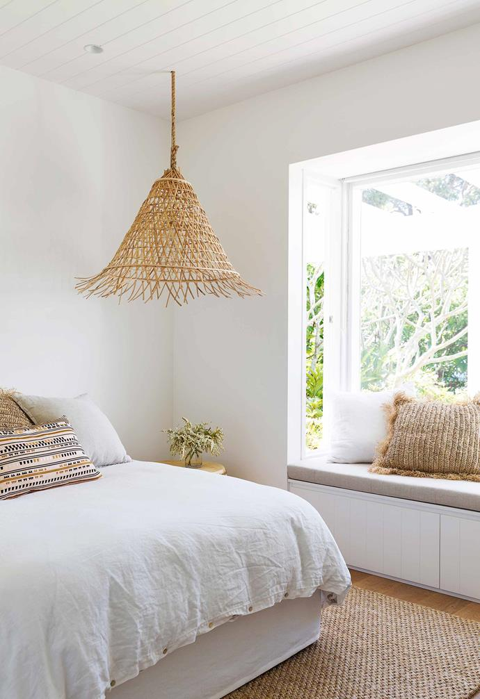 """Timber flooring and a jute rug complement the rattan pendant light shade in this bedroom in an [all-white fibro cottage](https://www.homestolove.com.au/fibro-cottage-avalon-20548