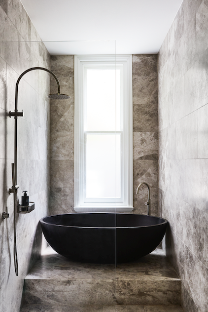 'Warm Tundra' limestone tiles from Signorino. *Bath* 'Haven' bath in Nero from Apaiser. *Bath tapware* Astra Walker 'Icon A69.08.V5' floor-mounted bath mixer. *Showerhead/tapware* Astra Walker 'Icon+ A67.24.V3' exposed shower with 200mm rose and hand shower and 'Icon A69.48' wall mixer, both in Brushed Platinum.