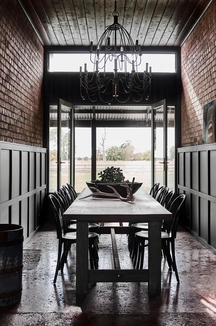 The breezeway, with its brick walls and concrete floor, was a cool retreat in hot weather for the original owners. The chandelier is a vintage  find and the dining table is made from timber salvaged from the breezeway roof. The ochre painting on the right is by Kimberley artist Nancy Nodea.