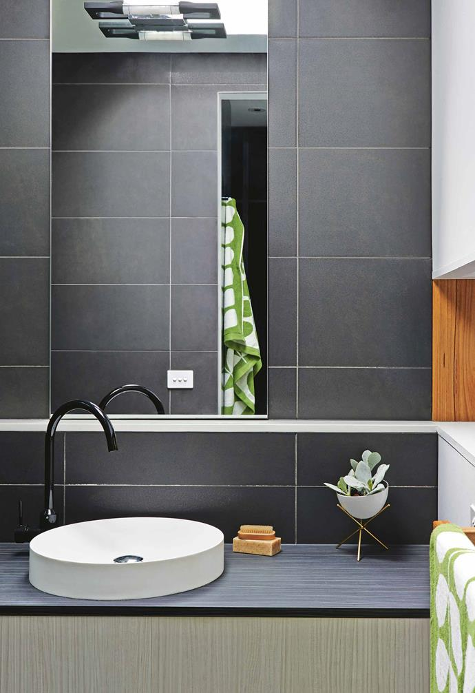 """**Small beauty** Large format grey tiles and a dark vanity make the Omvivo basin stand out in the ensuite. The finished result is sophisticated, but James didn't splurge. """"Simplicity was key because I didn't want any details with the tiles – I wanted something that was neutral and wouldn't date.""""<br><br>**Tip**: Pick which items are worth splashing out on and save elsewhere with fittings and luxe-look tiles."""