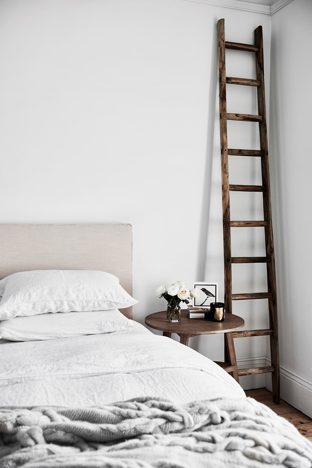 White walls and bedding in neutral tones give this bedroom a fresh feeling. A decorative ladder doubles as storage.