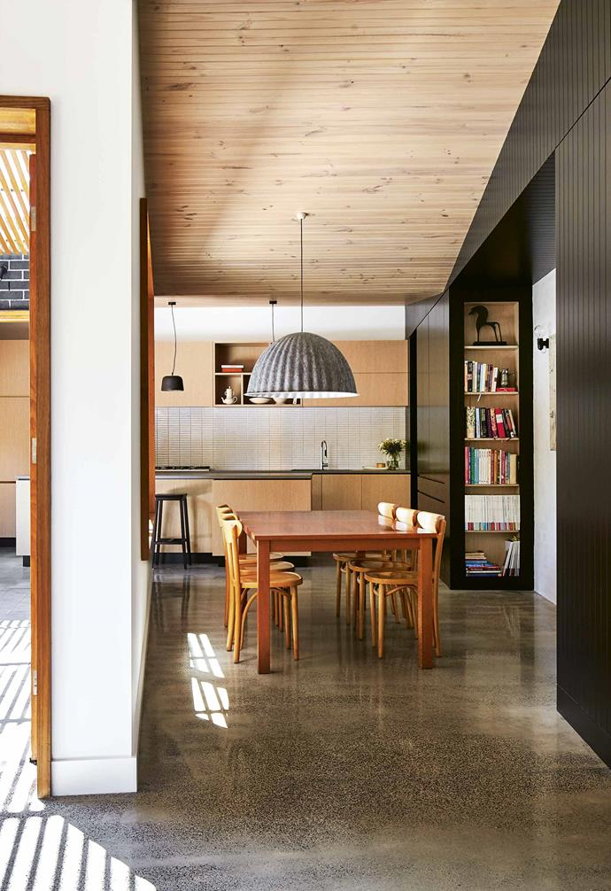 "**Open-plan living** Black joinery has been used to connect spaces and accentuate the shifts in ceiling height. ""The existing brick walls that connect the old and new spaces have been lightly bagged to showcase the texture,"" says the project's architect Melissa Bright. The limed timber ceiling boards provide warmth and soften the polished concrete floor."