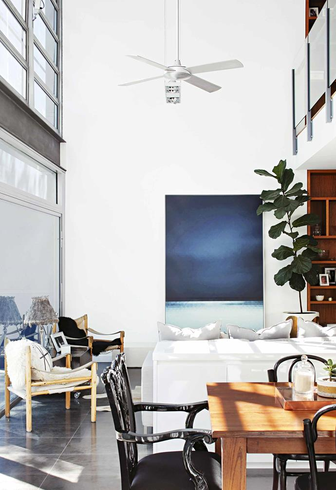 """The result is a void that both separates and connects the areas. """"It's like there is a bridge over to our bedroom,"""" explains Anoushka. """"There's room to get away and have some quiet time if you want to, but the open layout means we are still together.""""<br><br>**Living area** Thanks to glass sliders, two original Arne Norell 'Safari' chairs from Vampt Vintage Design appear to almost nestle into the bordering park."""