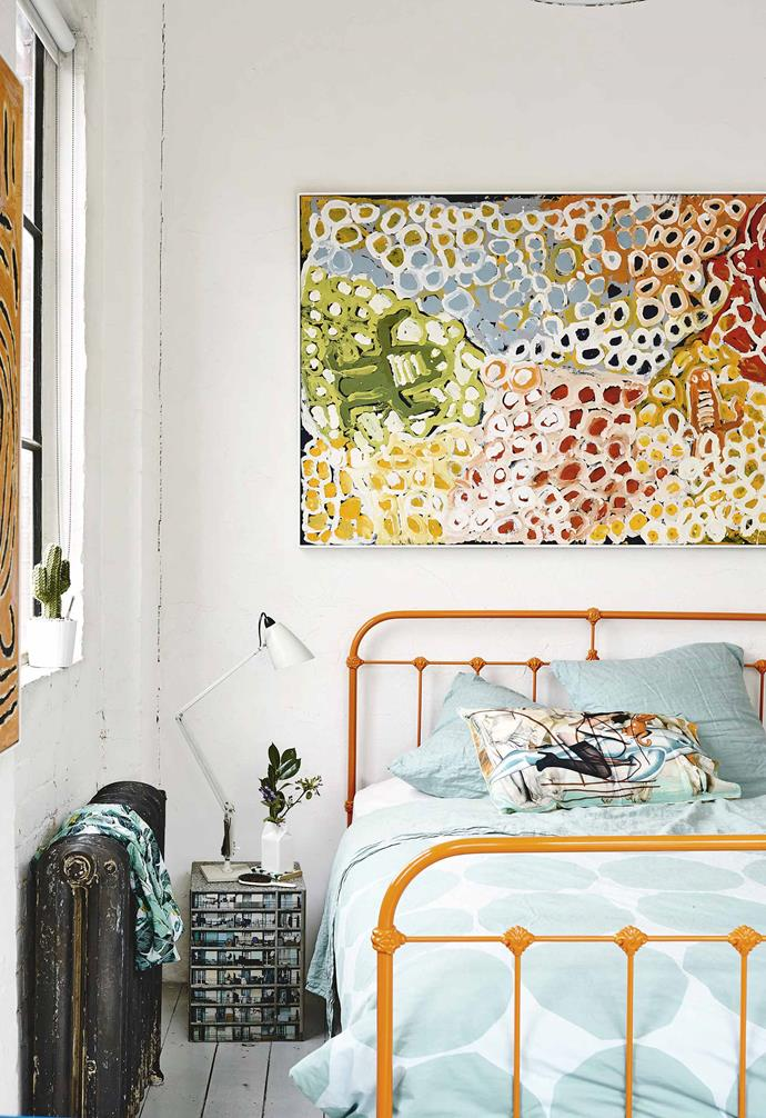 """""""I have everything here from old rag rugs discovered in Turkey to disused wooden crates that I've converted into drawers. I've just accumulated stuff over time and found my own style along the way,"""" says Saskia.<br><br>**Saskia's bedroom** An orange bed frame from Scout House was chosen by Saskia to match the artworks in the space."""