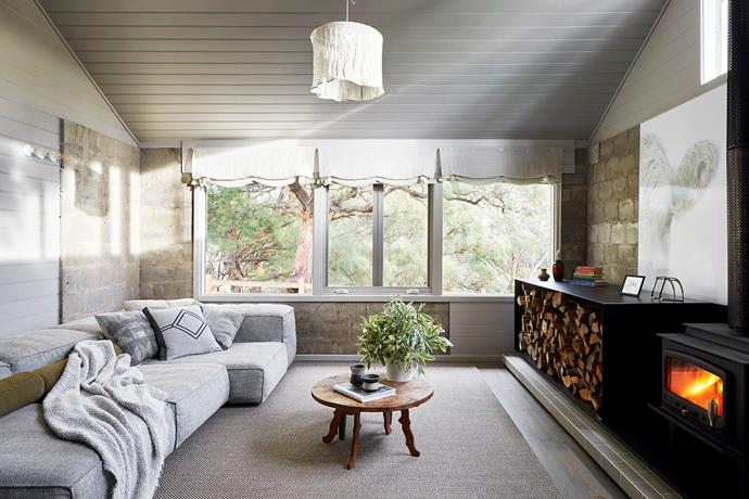 With its stacked logs and fireplace, the open living area is an unfussy, cosy space.