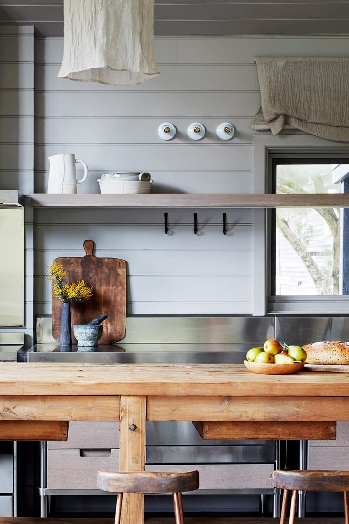 The gorgeous timber bench on castors is from Fossil Vintage. Stainless steel kitchen benches offer a nod to the home's origins. The white lights are from Fat Shack Vintage; blind made by Eclipse Window Furnishings.