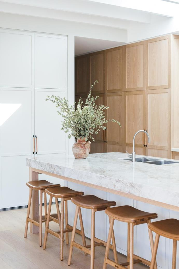 "The centrepiece of the open kitchen is the 100mm slab of Cosentino Dekton Taga stone on the island bench. ""Its lovely muted tones complement the oak cabinetry,"" says Kara. The oak and leather bar stools are from [GlobeWest](https://www.globewest.com.au/sketch-odd-leather-barstools