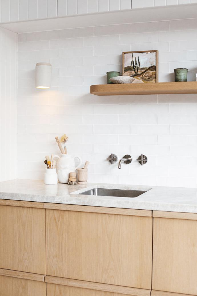 It may be small in size, but the guesthouse kitchenette makes up for it in style. Oak cabinetry is topped with a luxe stone benchtop and matte chalky-finished tiles have been used for the splashback. The floating shelf is the perfect place for Kara to put some of her favourite handmade ceramics and art on display in the studio