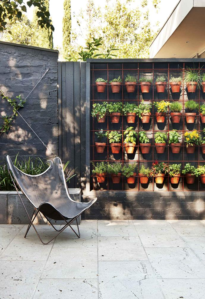 "The horizontal and vertical rods are welded and drilled into the frame to support the collected weight of the terracotta pots filled with herbs in this stacked herb [vertical garden](https://www.homestolove.com.au/vertical-garden-ideas-18432|target=""_blank"") installation."