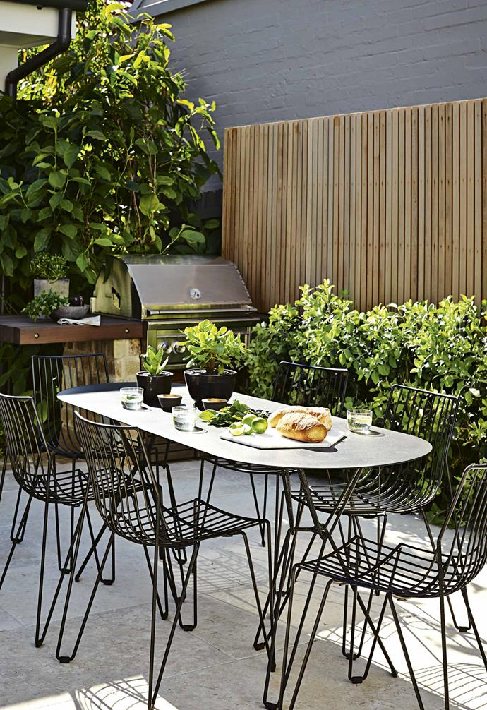 """The earthy tones of the fence's western red cedar palings complement the sandstone elements, while the dark [spotted gum decking](https://www.homestolove.com.au/outdoor-deck-tips-14347