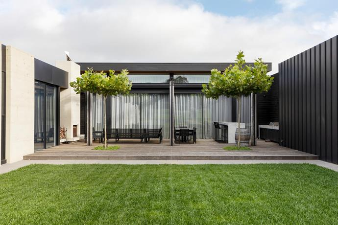 Two statuesque London plane trees (Platanus × acerifolia) stand proud within the outdoor dining area's timber deck. The manicured lawn completes the beautifully composed scene.