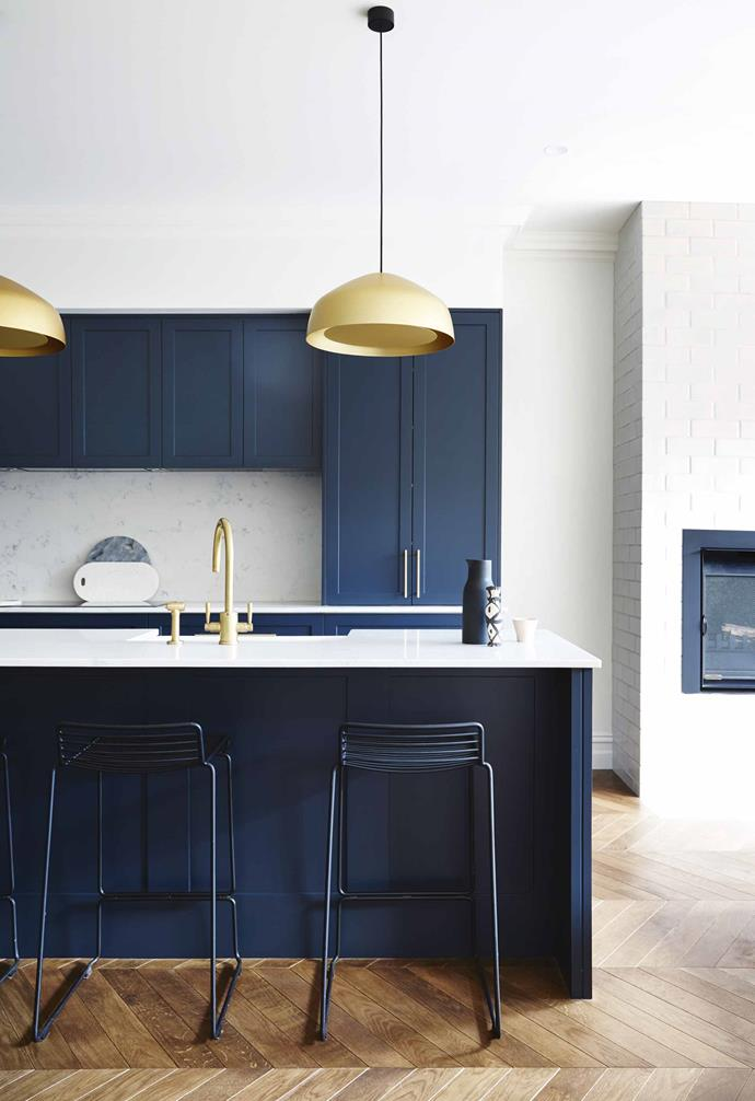 "This [traditional Edwardian semi was given a contemporary revamp](https://www.homestolove.com.au/modern-edwardian-semi-renovation-18524|target=""_blank"") which extended to its open-plan kitchen living and dining space. In the kitchen, shaker style cabinetry in a bold blue was chosen to be the central feature, with sculptural gold pendant lights and tapware adding a glamourous contrast."